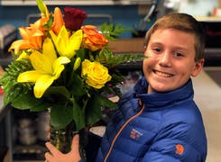 A young member of the Welke family holds a beautiful bouquet of red, yellow and orange roses
