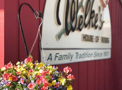 A bright, cheerful hanging floral arrangement stands before our store sign