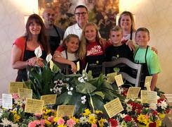Welke's store operators and floral designers pose with a group of young helpers